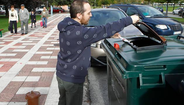 Kiko Sánchez Salazar abre con su llave el contenedor y deposita la bolsa con materia orgánica.