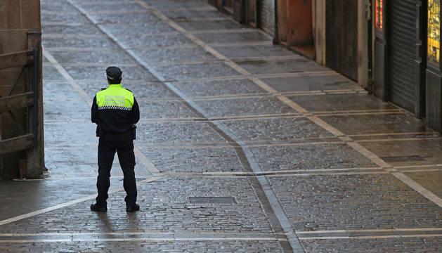 Un agente municipal con el jersey del uniforme en el recorrido del encierro de Pamplona.