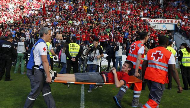 Voluntarios de Cruz Roja socorren a un aficionado de Osasuna tras la avalancha contra el Betis