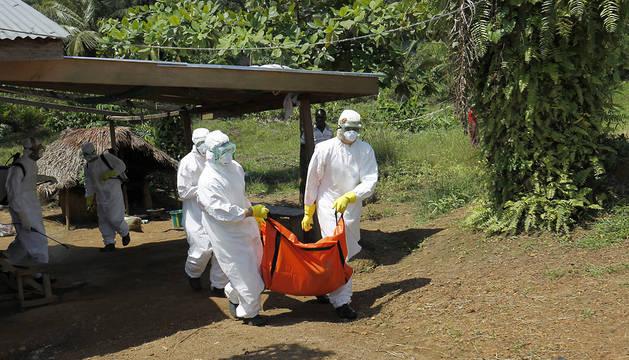 Varios sanitarios trasladan el cuerpo de un enfermo en Monrovia (Liberia).