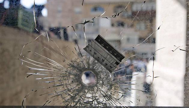 Vista de un agujero de bala en el cristal de la sinagoga del barrio ortodoxo de Har Nof, en Jerusalén