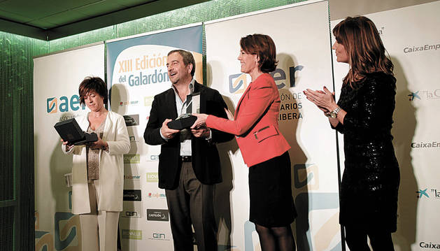 Yolanda Garbayo, premio al Relevo Generacional, observa su premio mientras Enrique Martínez recibe el suyo de manos de la presidenta del Gobierno de Navarra, Yolanda Barcina.