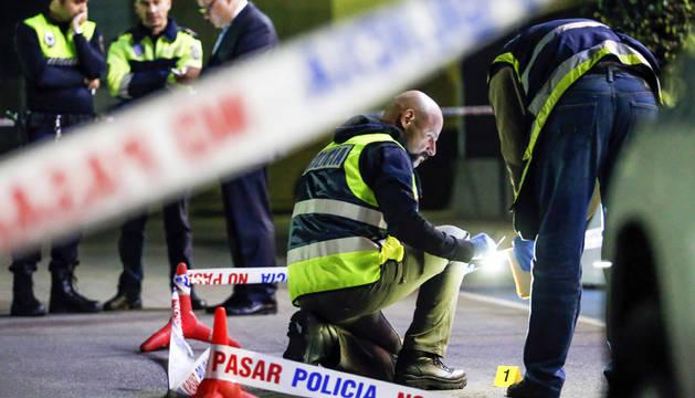 Dos policías recogen los casquillos de bala en la puerta del disco-pub