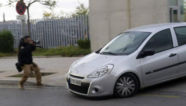 Un coche traslada a uno de los detenidos en Granada.