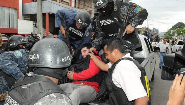 Policías hondureños custodian a Plutarco Ruiz, presunto responsable del crimen de la Miss Mundo Honduras.