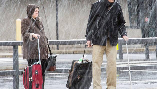 Dos personas, bajo la nieve en el exterior del aeropuerto de Washington, en el estado de Virginia