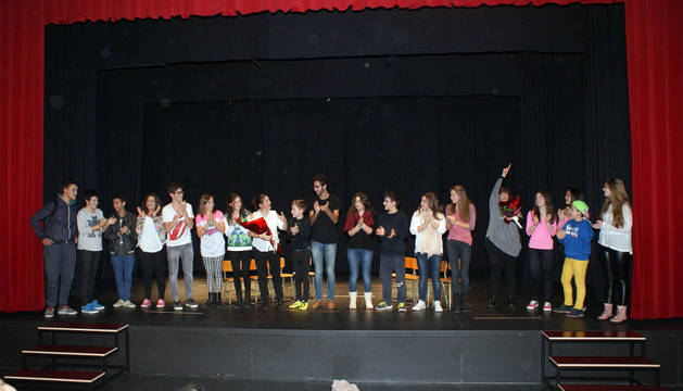Los miembros del grupo, acompañados por la directora y el equipo de producción, reciben la ovación del público tras la obra.