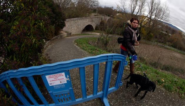 Una valla azul con un pequeño rótulo informa de la falta de alumbrado en este tramo del paseo fluvial.