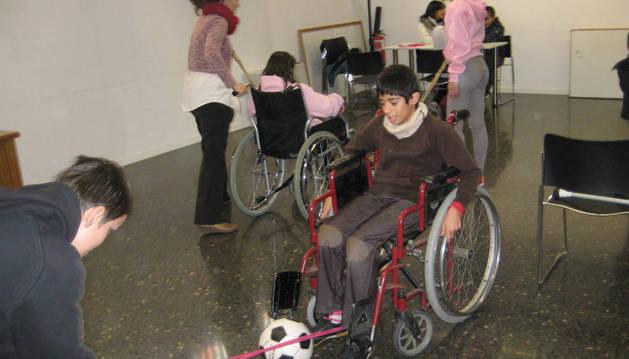 Un menor simula un ejercicio adaptado a personas discapacitadas