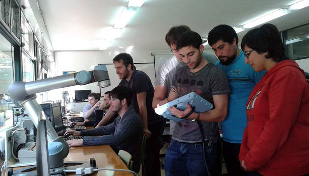 Un grupo de alumnos maneja el robot colaborativo