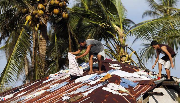 Dos filipinos tienden ropa en el tejado