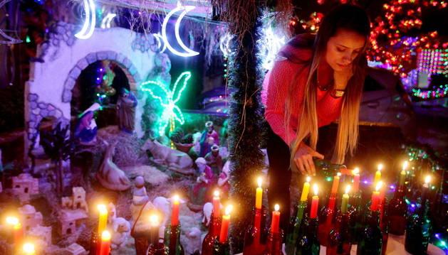Una mujer enciende velas durante la tradicional 'Noche de las Velitas'