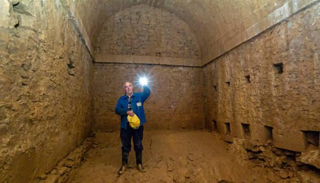 Carmelo Etxeberria Gil alumbra la sala de captación, donde se aprecian los agujeros en la pared (en línea) de entrada de agua.