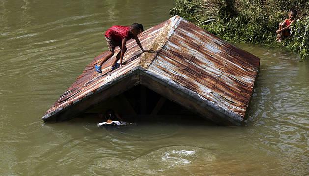 Unos niños trepan al tejado de una casa en la localidad de Taft