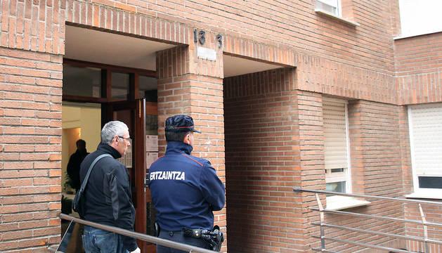 Agentes de la Ertzaintza, en el portal de la vivienda de la localidad vizcaína de Abadiño donde una mujer y su madre han sido halladas muertas