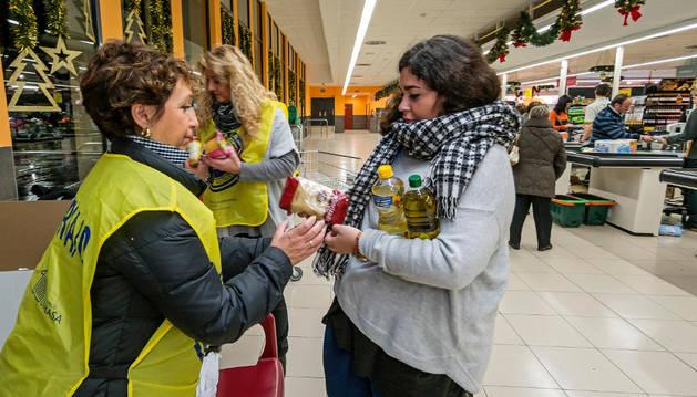Voluntarios recogen una de las aportaciones en el supermercado de Mercadona en Estella.