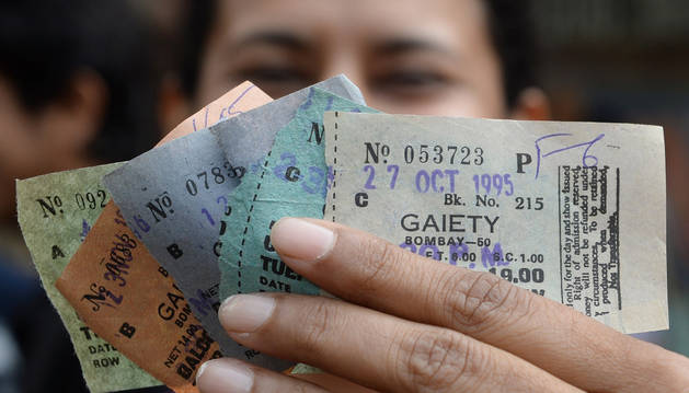 Una mujer muestra varias entradas para ver la película