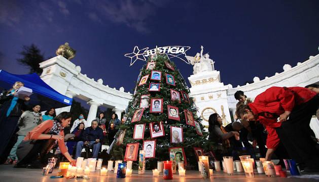Organizaciones civiles colocan velas en torno a un árbol navideño en  Ciudad de México con fotografías de los desaparecidos.