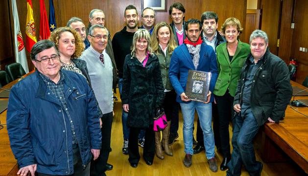 Iván Fandiño, con el libro de Estella, en el salón de plenos con concejales y miembros del club taurino