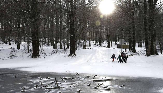 Un grupo de personas, caminando junto a una charca helada en Urbasa.