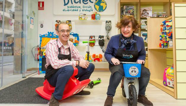 Javier Lacasia, un un balancín, y Cristina Fernández, en una bicicleta, en la tienda Dideco, que han abierto en el Ensanche.