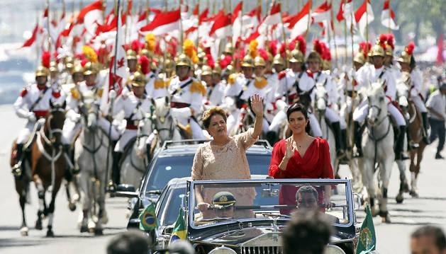 La presidente brasileña, Dilma Rousseff, saluda desde el coche junto a su hija