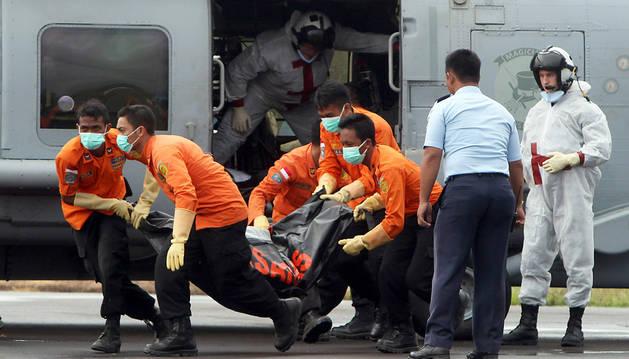 Los equipos de rescate trasladan un cuerpo.