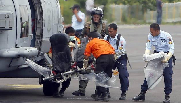 Un equipo de rescate transporta uno de los asientos del avión siniestrado