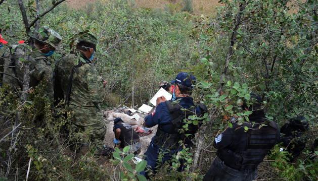 Peritos forenses y militares realizan el levantamiento de los cadáveres