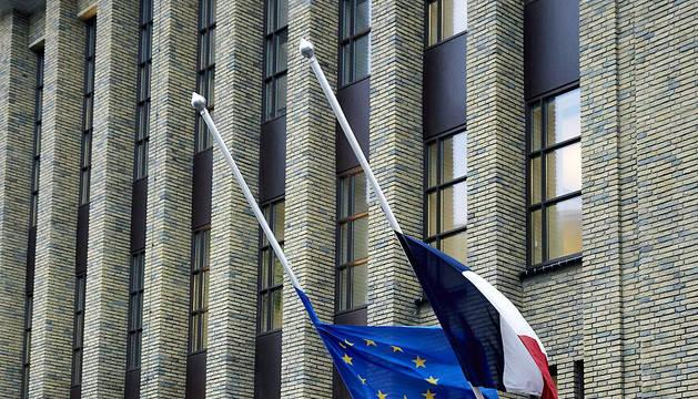 La bandera de Francia (d) y de la Unión Europea (UE) ondean a media asta en la embajada de Francia en la Haya (Holanda)