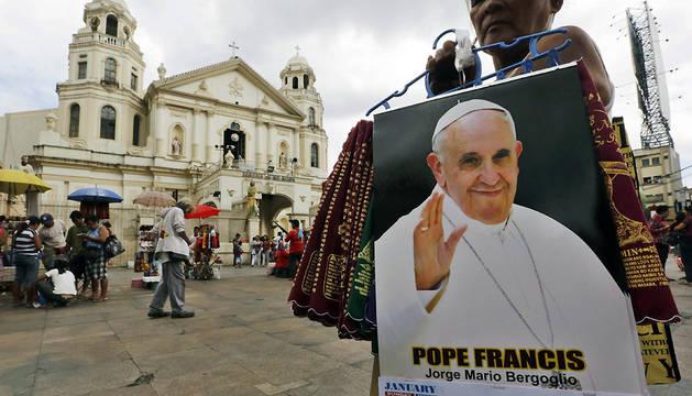Una vendedora ambulante filipina ofrece calendarios con la foto del papa Francisco frente a una iglesia en Manila (Filipinas)