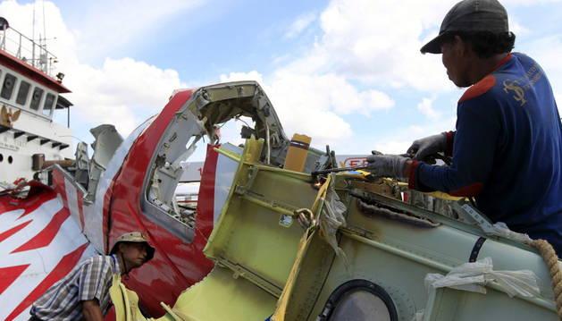 Los trabajadores inspeccionan los restos del avión