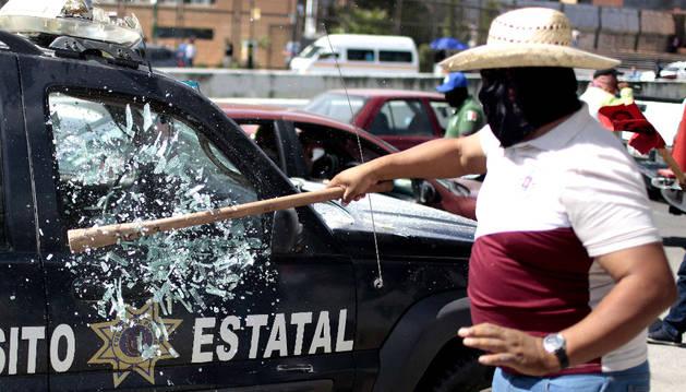 Un manifestante rompe los cristales de un coche patrulla.