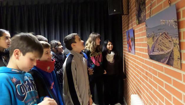 Varios alumnos observan algunas de las fotos de la exposición