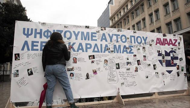 Una mujer escribe en un panel colocado para plasmar eslóganes electorales
