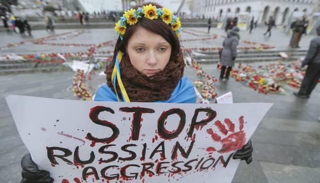 Una ucrania con un cartel de 'Detener la agresión rusa'