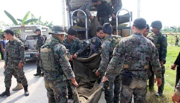 Miembros de la policía portan el cadáver de un agente muerto