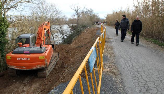 Varios vecinos contemplan los trabajos que realiza una excavadora para reparar el camino.