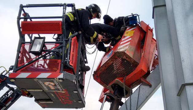 Momento en el que un bombero coloca el arnés de seguridad al operario.