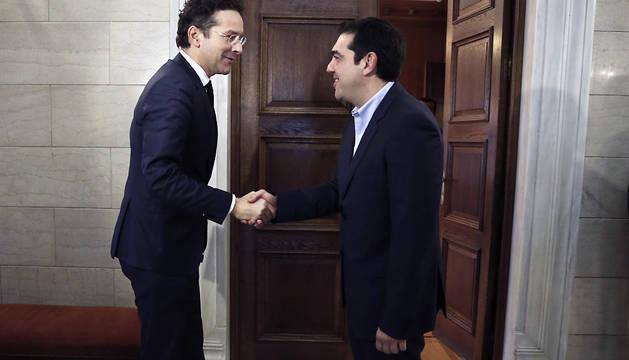 El primer ministro griego, Alexis Tsipras (dcha), durante la reunión con el presidente del Eurogrupo, Jeroen Dijsselbloem
