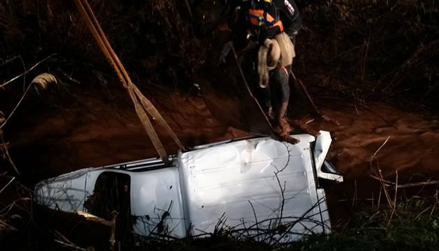 Momento en el que es izado el vehículo arrastrado por el río Odrón en Los Arcos.