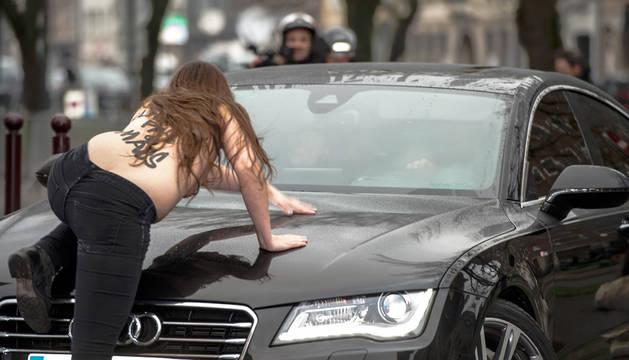 Una activista de Femen se abalanza sobre el coche de Strauss-Kahn a su llegada al tribunal.