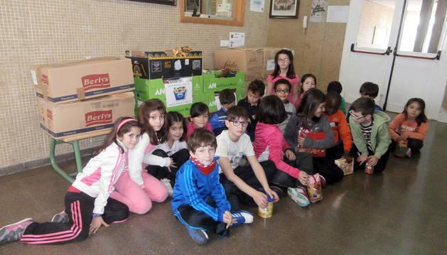 Un grupo de niños posa junto a los alimentos recogidos.