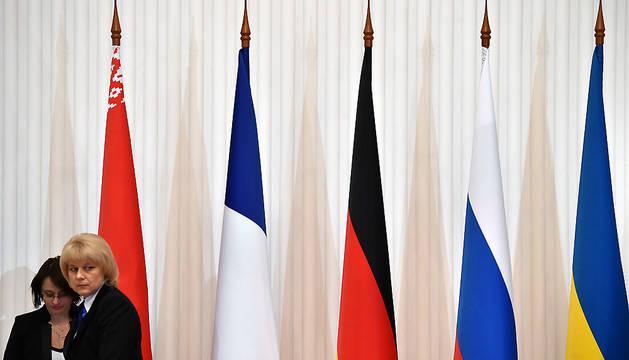 Una mujer pasa junto a las banderas de los países participantes en la cumbre de Minsk sobre Ucrania