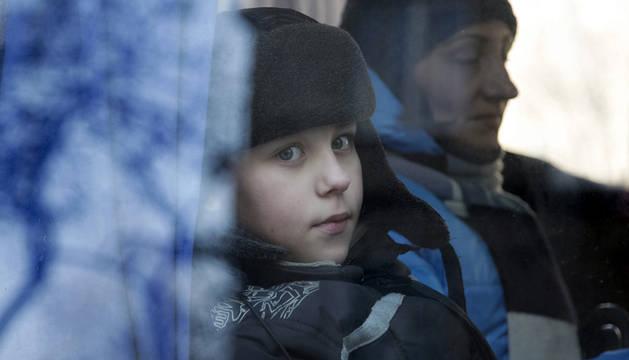 Una niño mira a través de la ventanilla mientras espera a ser evacuado a Rusia en un autobús desde Donetsk.