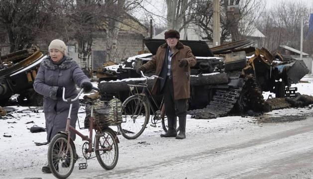Dos personas pasan junto a los restos de vehículos militares en Uglegorsk, en el área de Donetsk (Ucrania)