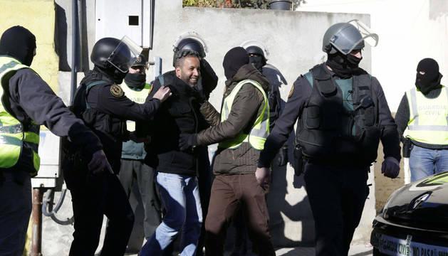 Agentes de la Guardia Civil trasladan a uno de los cuatro detenidos en una operación en la que se ha desarticulado una red de reclutamiento y adoctrinamiento del grupo terrorista yihadista DAESH en España, en una acción en la que han detenido a dos person