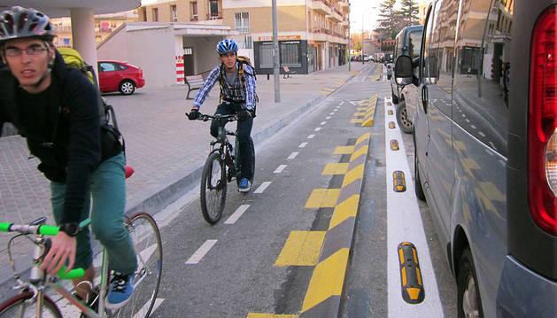 Dos ciclistas circulan por el carril bici de la calle Gayarre, modificado para evitar golpes con los coches.
