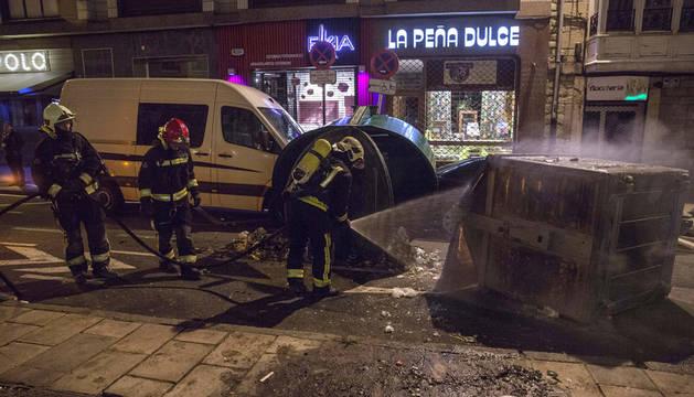 Los bomberos apagan un contenedor volcado e incendiado durante los incidentes producidos en Vitoria