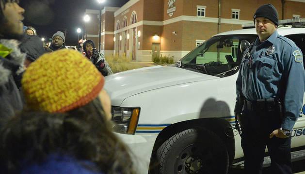 Un policía de Ferguson, frente a varias personas que protestan por la decisión.